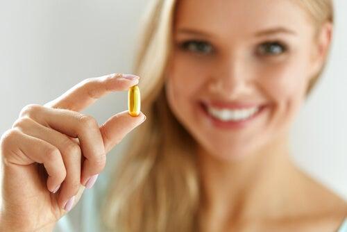Mulher tomando vitaminas para evitar resfriados no inverno