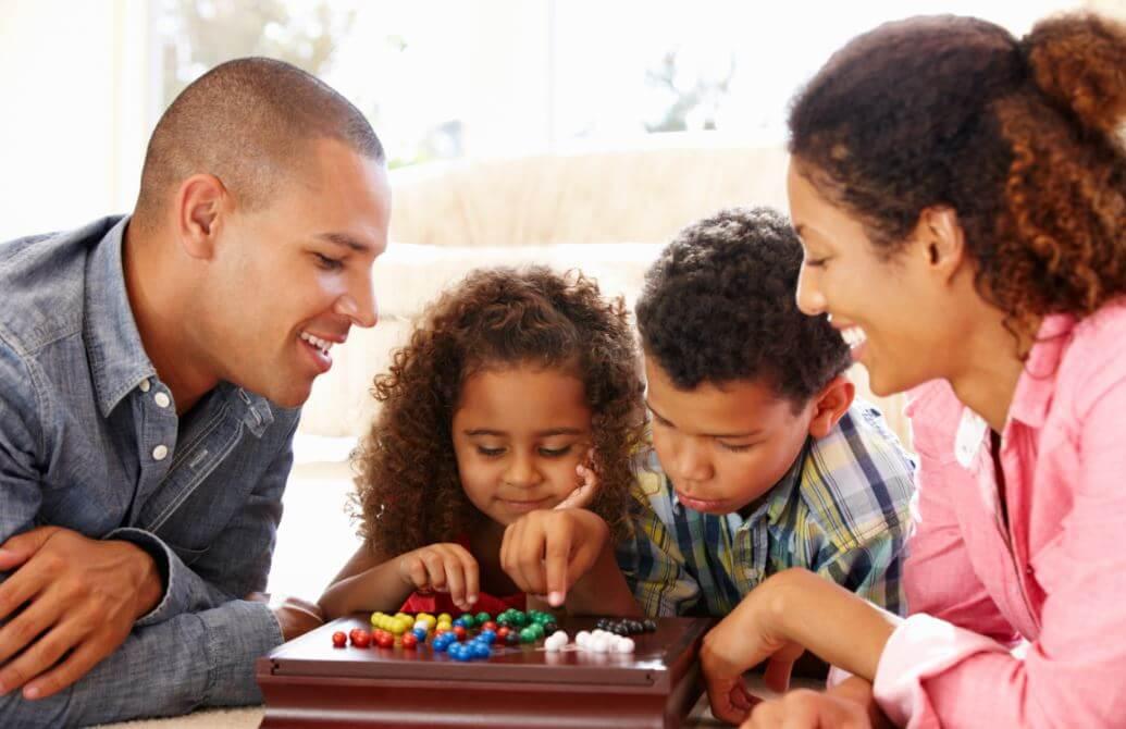 Familia divirtiéndose con juegos de mesa.