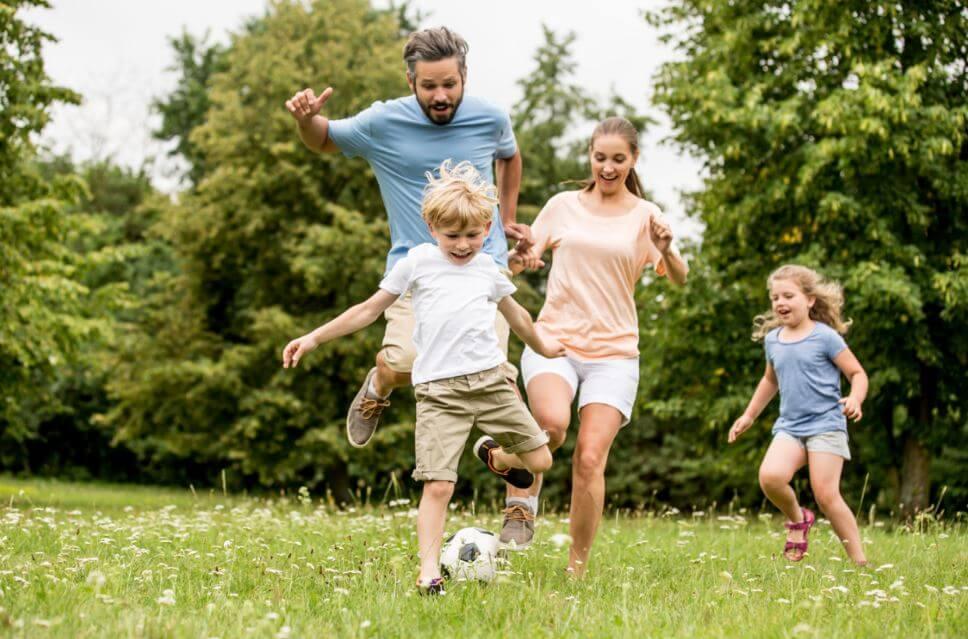 Padre y sus tres hijos jugando con el balón en el jardín de su casa