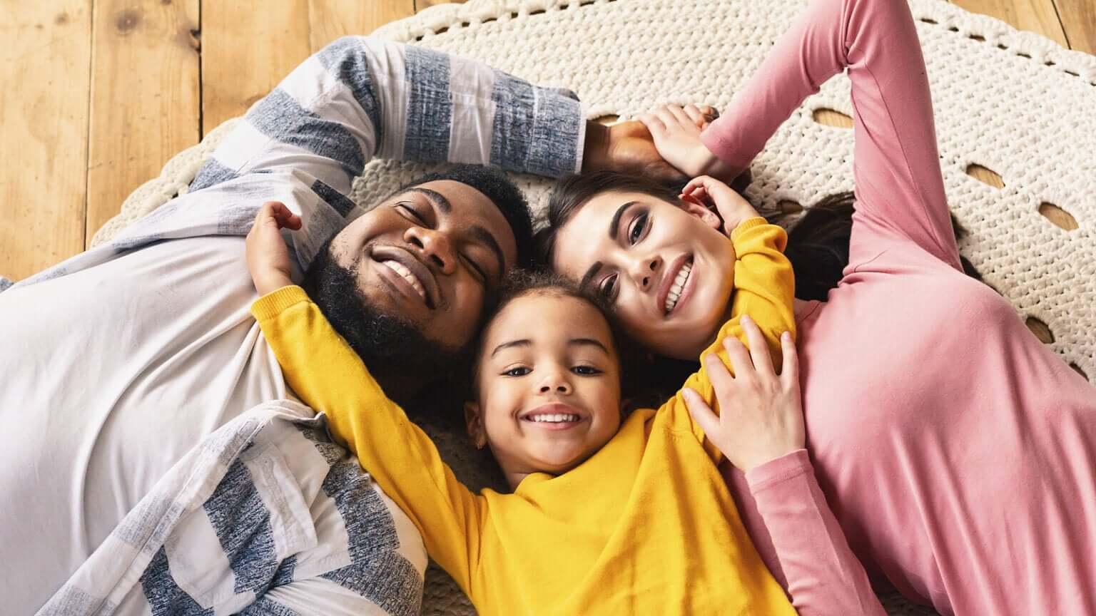 Familia unida tumbada en el suelo.