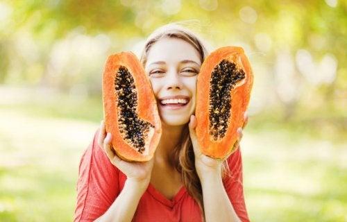 mujer sosteniendo dos mitades de papaya