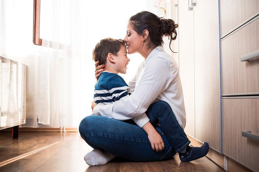 Madre dándole un beso en la frente a su hijo