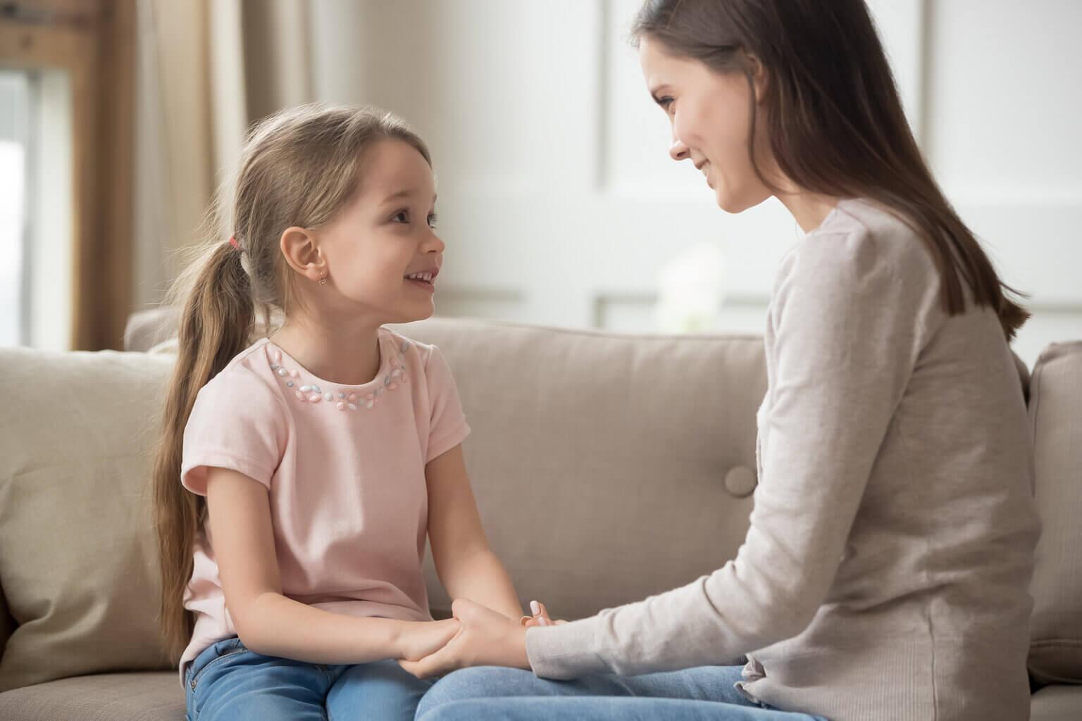 Madre hablando con su hija de forma positiva.