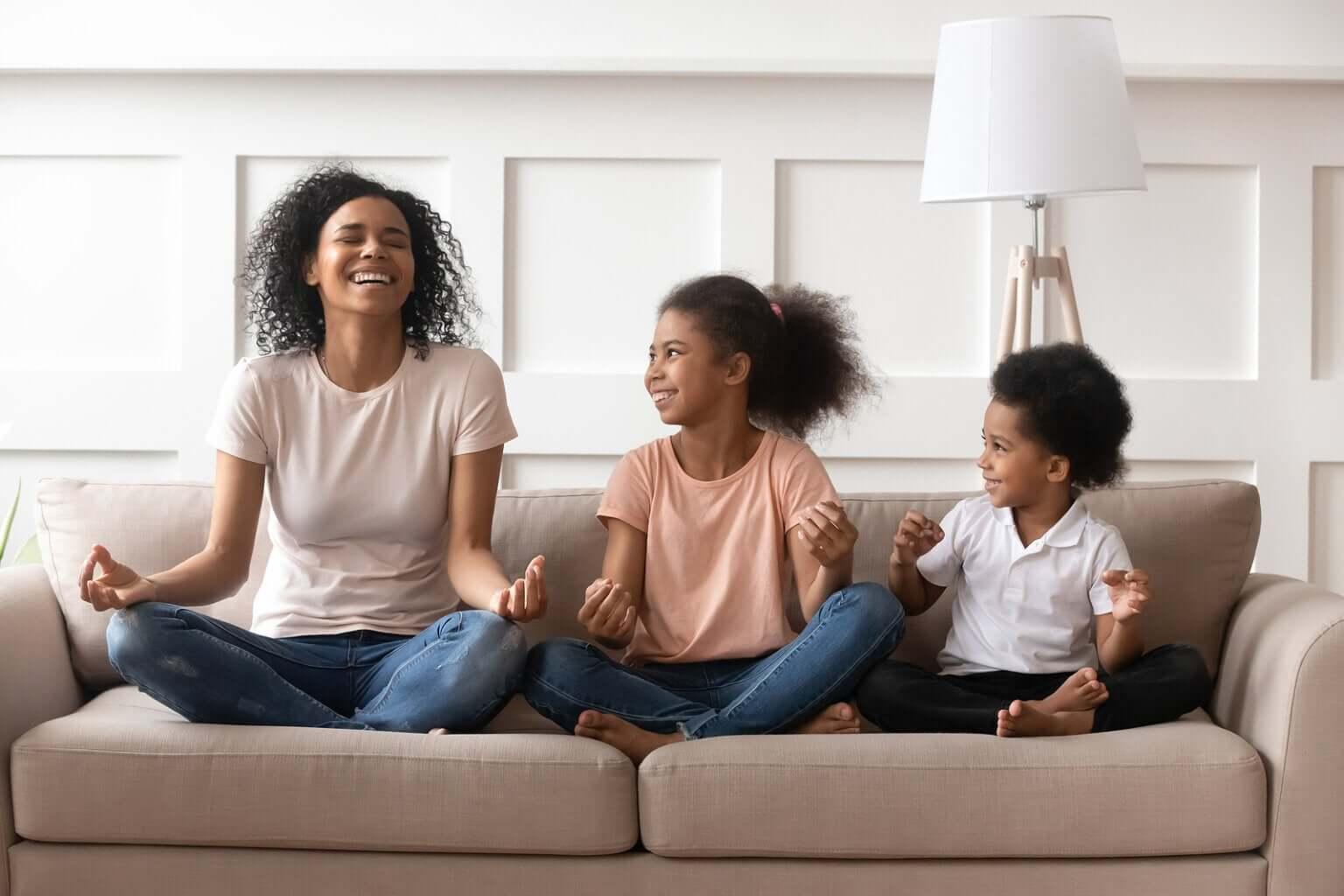 Madre con sus hijos riendo y meditando.