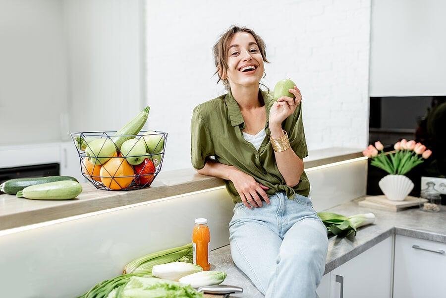 Mujer en la cocina con vegetales alrededor.