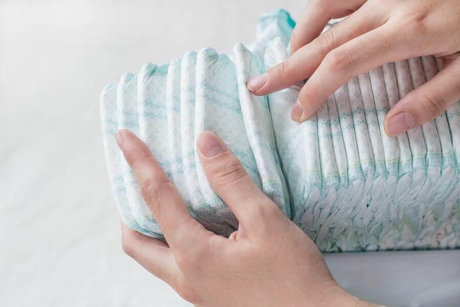 Mujer con pañales de bebé en las manos