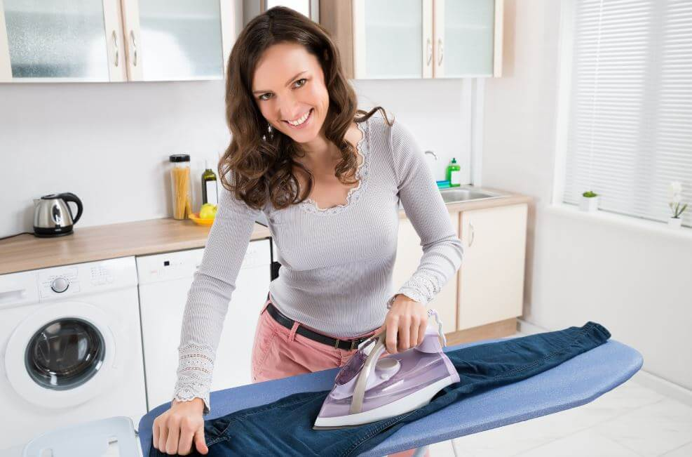 Mujer planchando unos pantalones vaqueros.