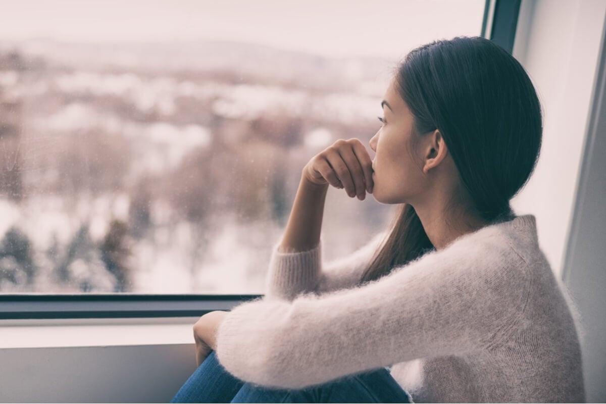 Mujer sola mirando por la ventana