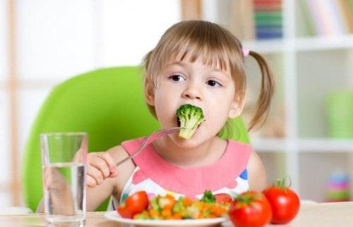 Una niña pequeña come brócoli.