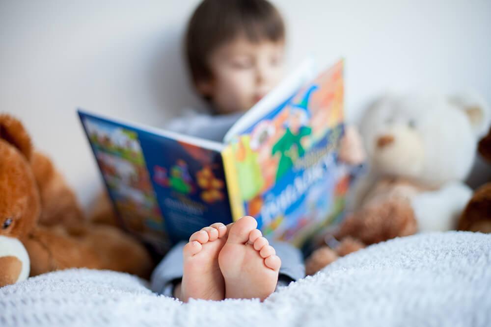 Niño sentado en la cama rodeado de peluches lee un cuento infantil.