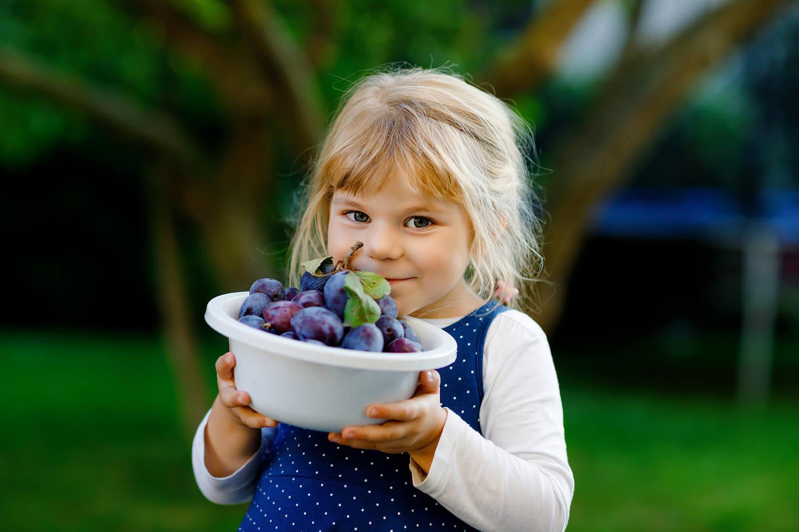 Niña con un bol de uvas.