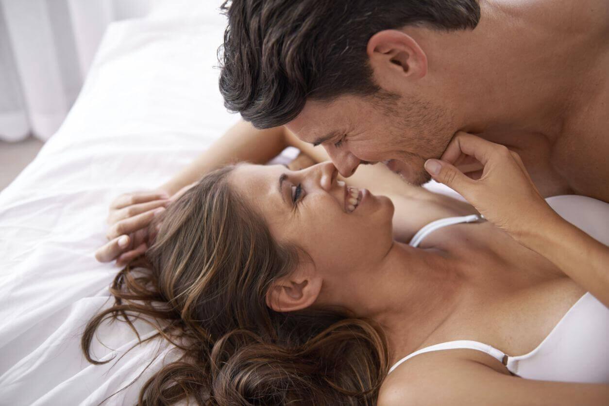 Pareja en la cama a punto de besarse