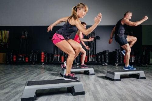 Personas en el gimnasio haciendo ejercicio aeróbico.