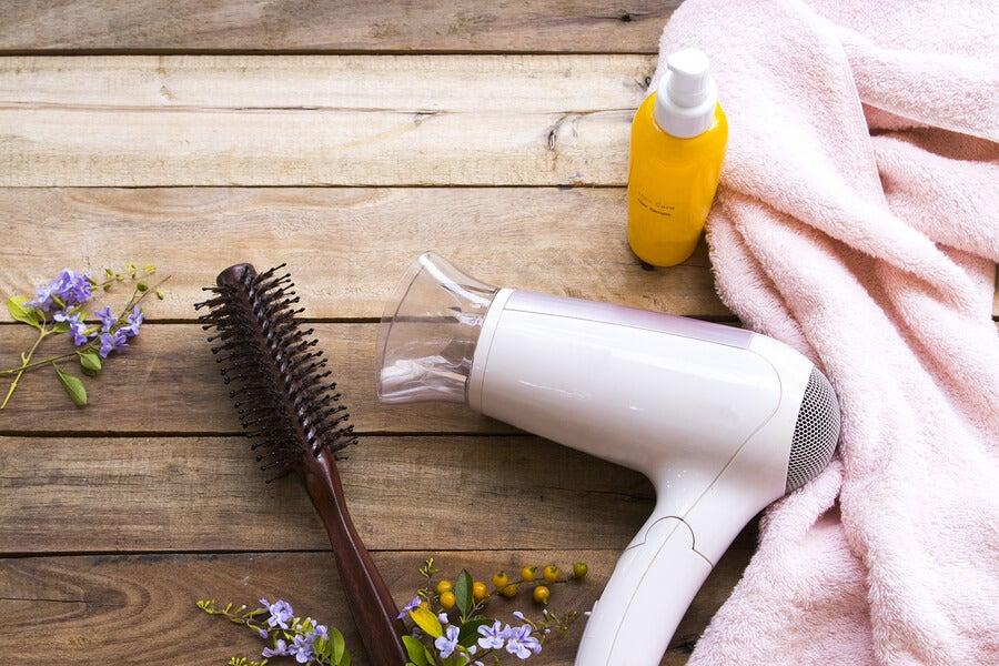 Secador y cepillo de pelo junto a un bote de sérum