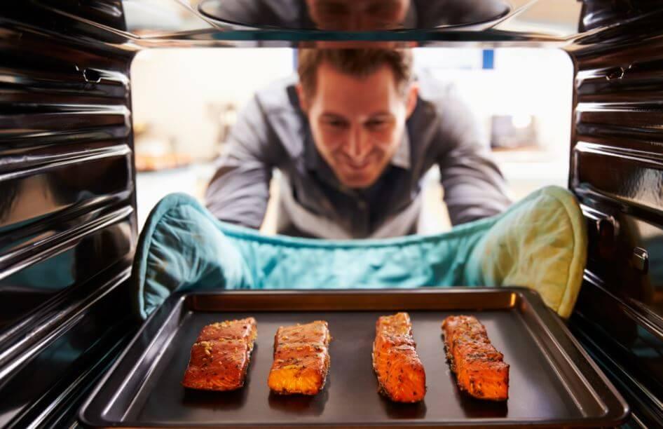 Hombre introduciendo una bandeja con salmón al horno.