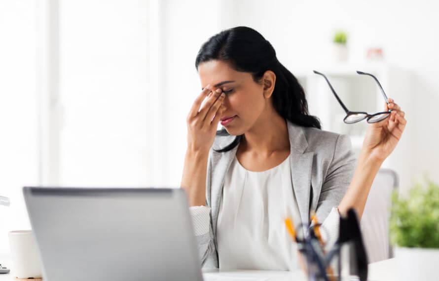 Mujer joven se ha quitado las gafas y se frota los ojos con el ordenador delante.