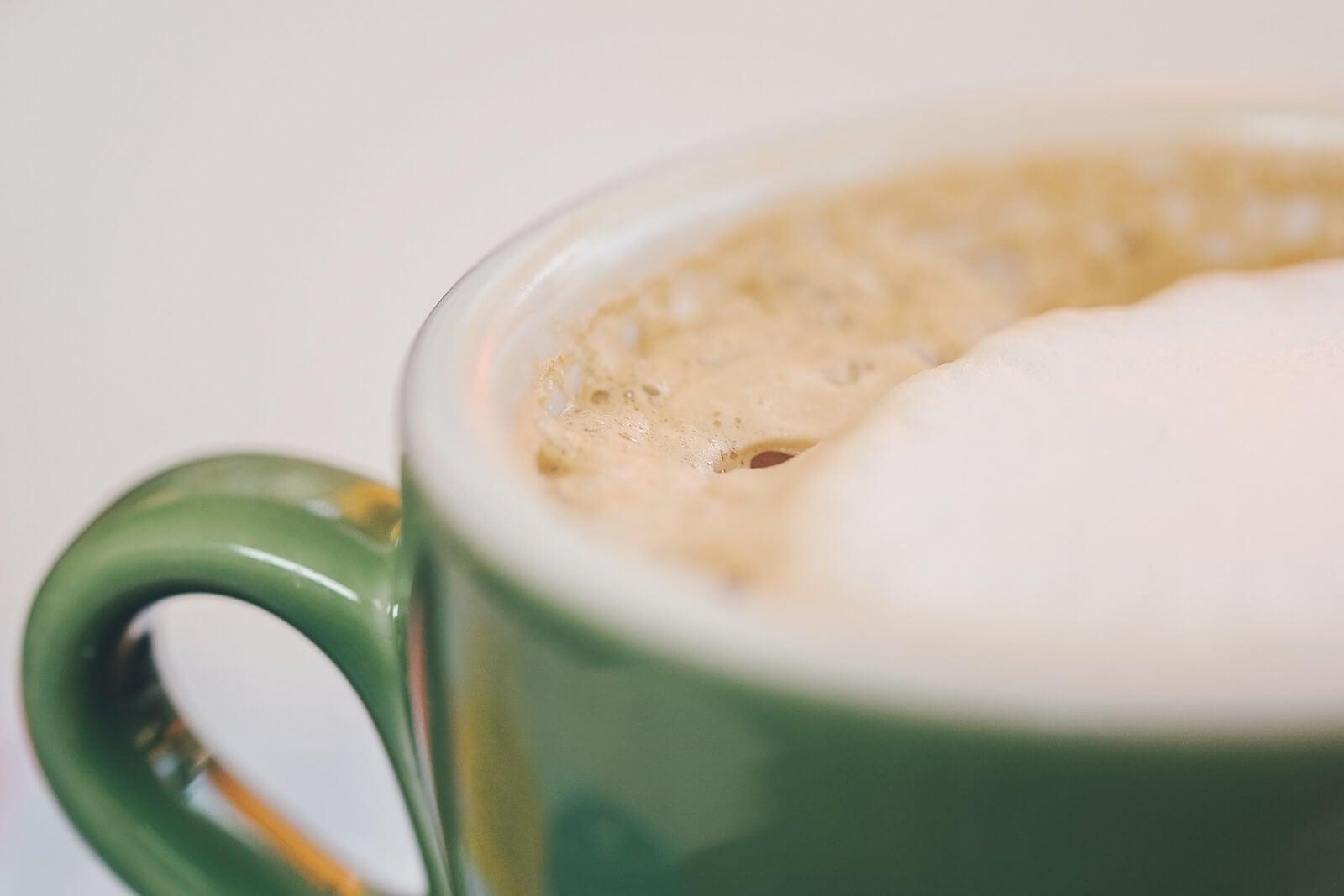 Taza verde con café y leche.