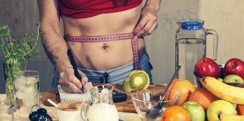 Productos para adelgazar: midiéndose el abdomen y apuntando en una libreta junto con alimentos