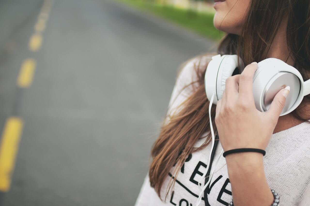 Chica con cascos blancos para escuchar música