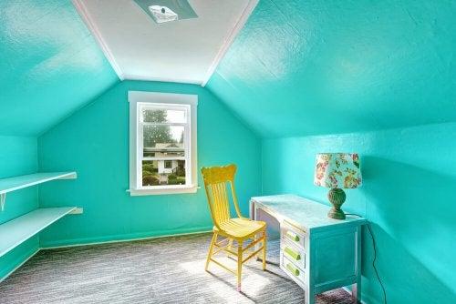 Habitación con paredes de un azul vibrante con un escritorio, una lámpara y una silla amarila