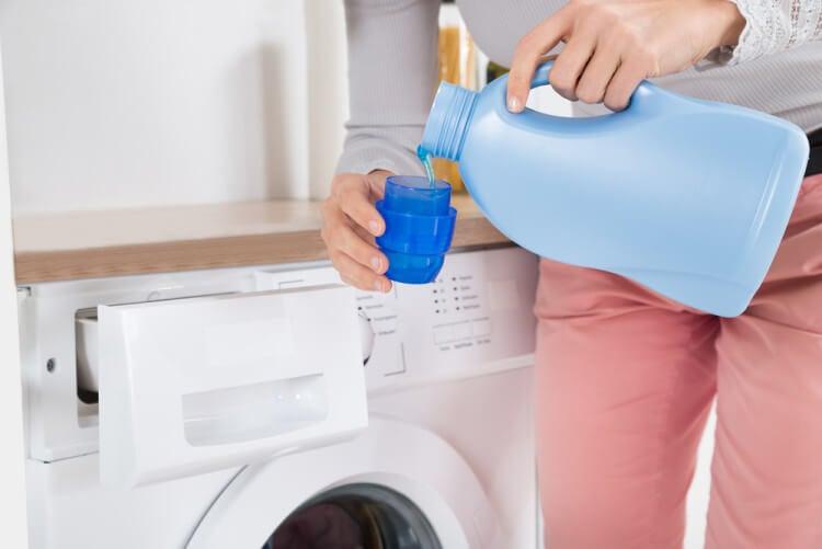 Mujer echando detergente a la lavadora