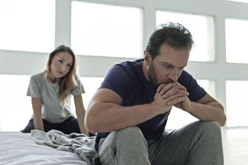 Hombre pensativo sentado en la cama mientras su mujer le mira preocupada: disfunción sexual en la diabetes