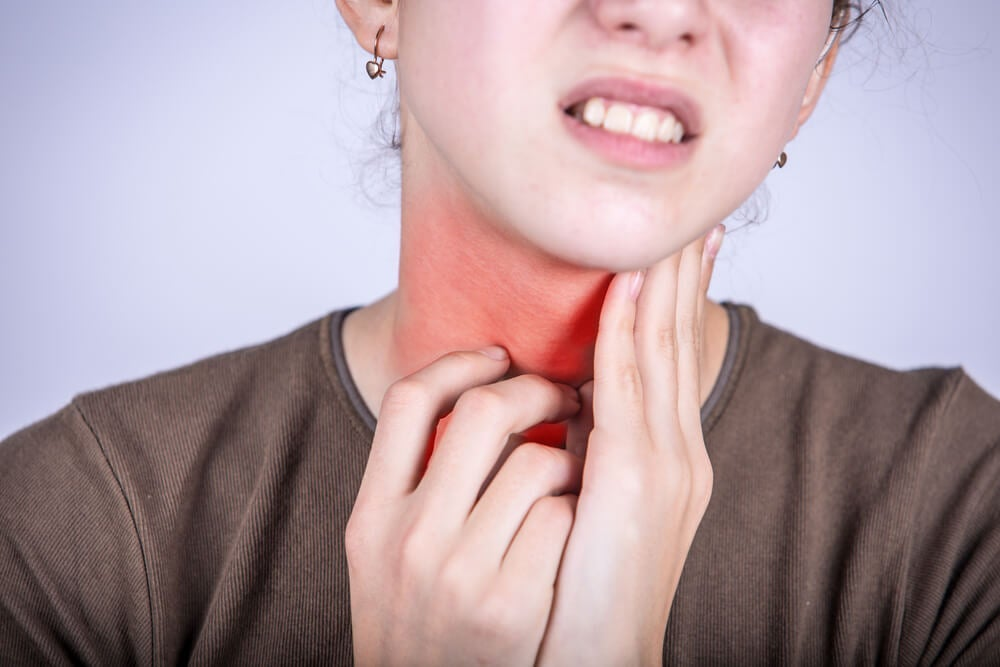 Mujer con la garganta inflamada. Uno de los síntomas de la faringitis.