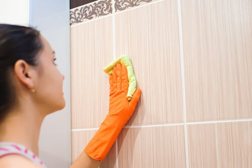Mujer limpiando los azulejos.