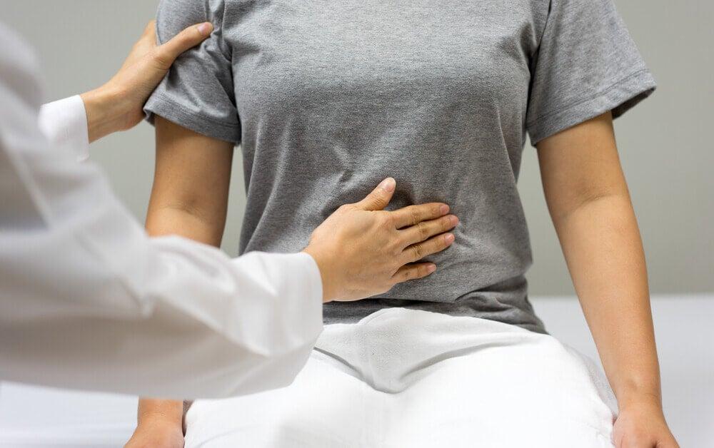 Médico poniendo una mano en el abdomen de una paciente.