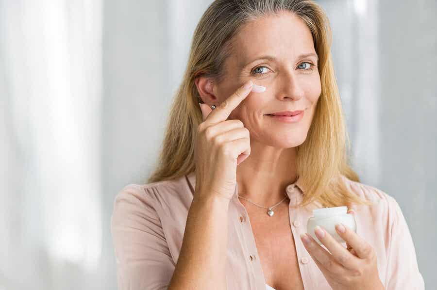 Mujer aplicándose crema hidratante.