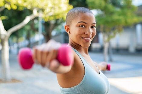 Mujer haciendo ejercicios con las mancuernas para trabajar los deltoides y desarrollar masa muscular en los brazos..