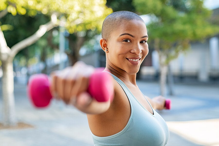 Mujer haciendo ejercicios con las mancuernas para trabajar los deltoides.