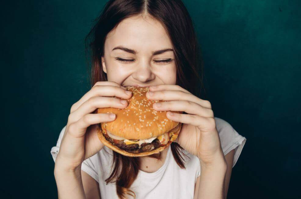 Woman eating a hamburger.