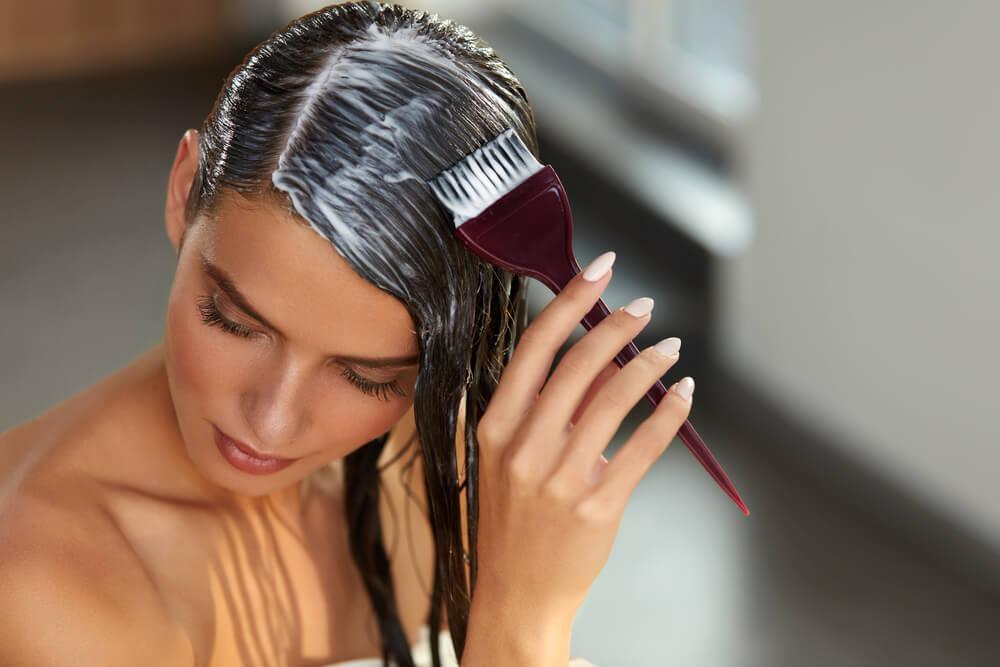 Mujer aplicándose mascarilla en el pelo con ayuda de un peine en forma de pincel.