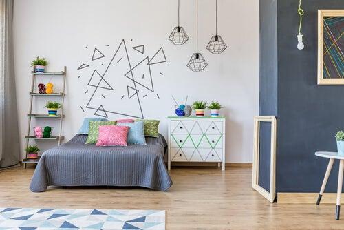 Habitación con un mural infantil en la pared a base de triángulos de distintos tamaños y en diferentes orientaciones