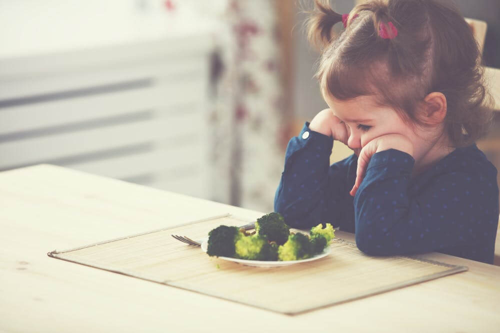 Niña con neofobia alimentaria delante de un plato de brócoli