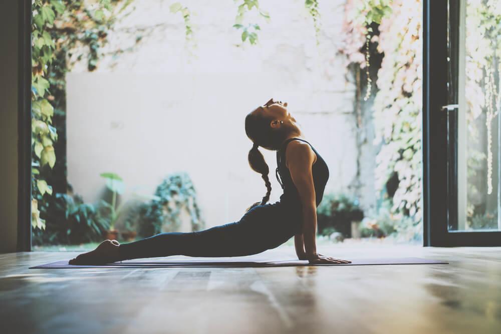 mujer practicando las posturas de yoga para la felicidad