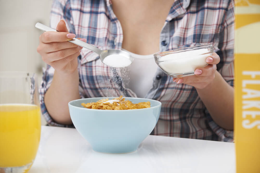 Mujer tomando un bol de cereales con azúcar.