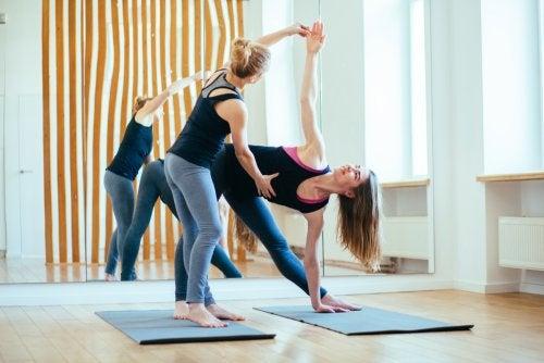 Mujer haciendo yoga siendo instruida