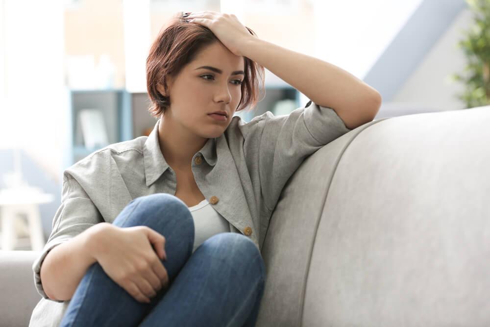 Mujer joven rodea sus piernas con una mano y apoya la otra en su cabeza, pensativa, mientras está sentada en el sofá.