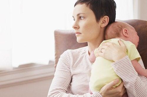 Mujer con un bebé mirando por la ventana
