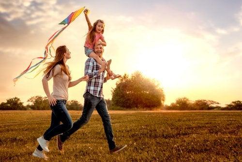 Familia contenta por el campo con una cometa