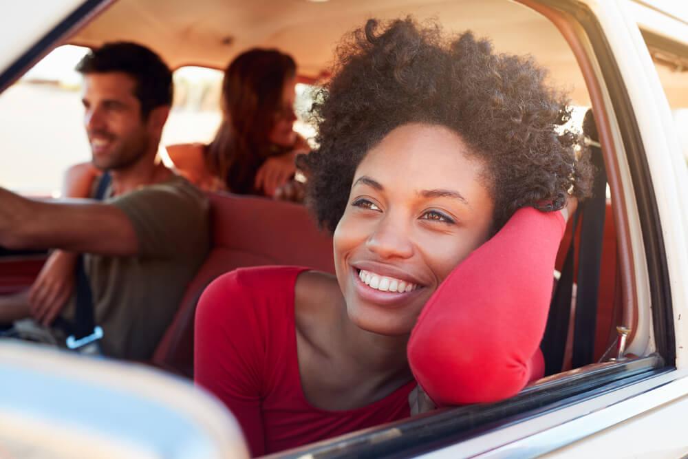 Mujer sonriente apoyada en la ventanilla de un coche yendo de viaje con amigos.