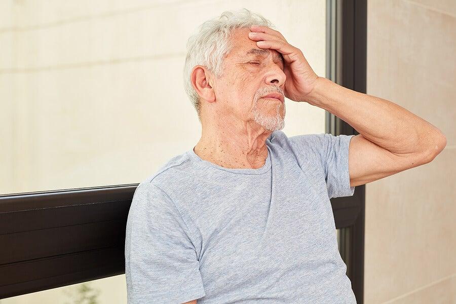 Hombre mayor con dolor de cabeza y mareo.