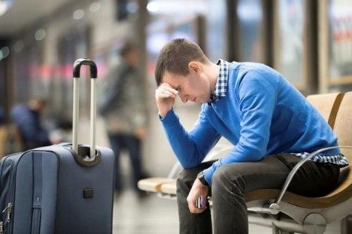 Hombre frente a su maleta, sufriendo jet lag.