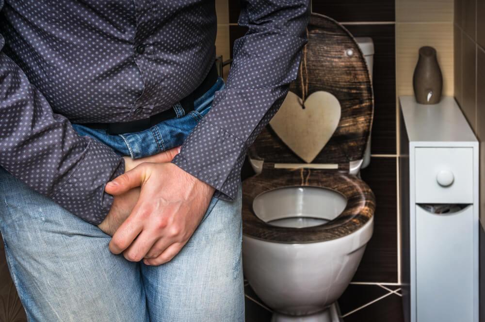 Hombre en el cuarto de baño con las manos en la zona genital: sonda Foley para incontinencia urinaria