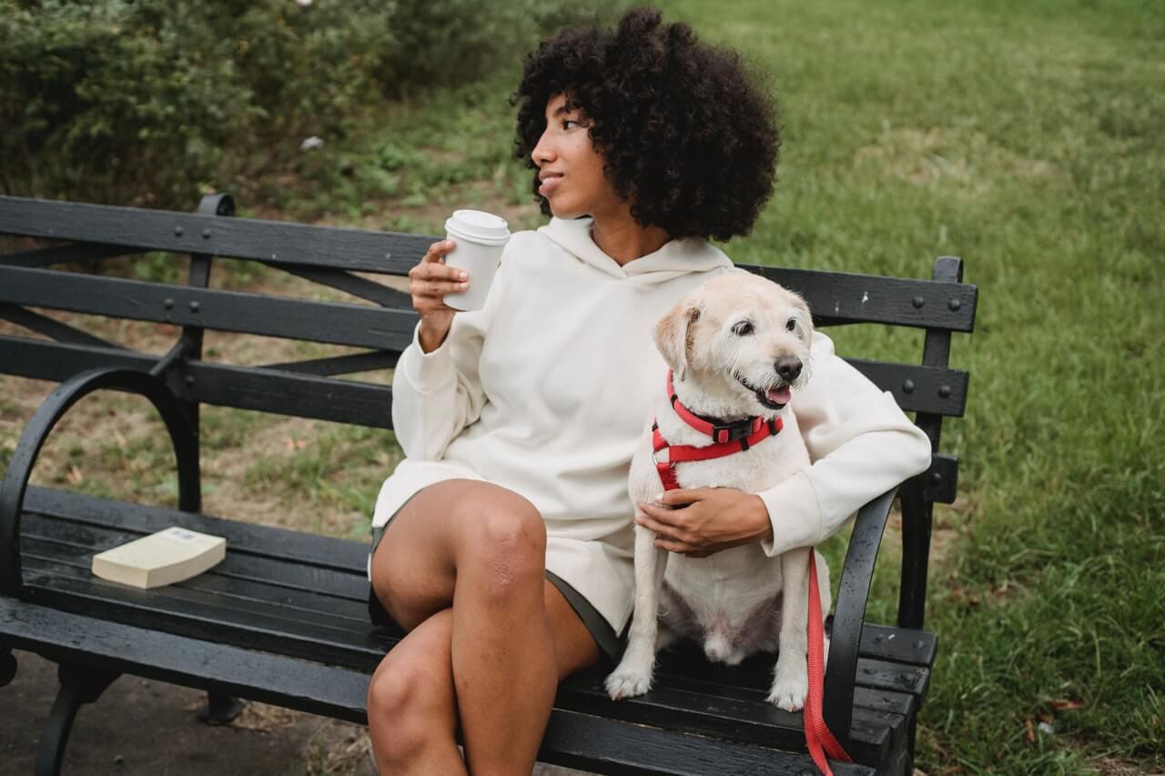 Mujer con perro en un banco del parque.