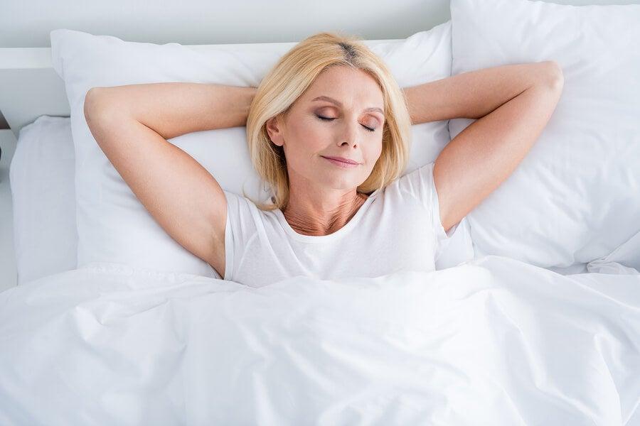 Mujer descansando en su cama bocaarriba