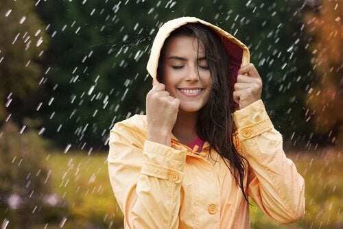mujer bajo la lluvia feliz por prevenir la ansiedad
