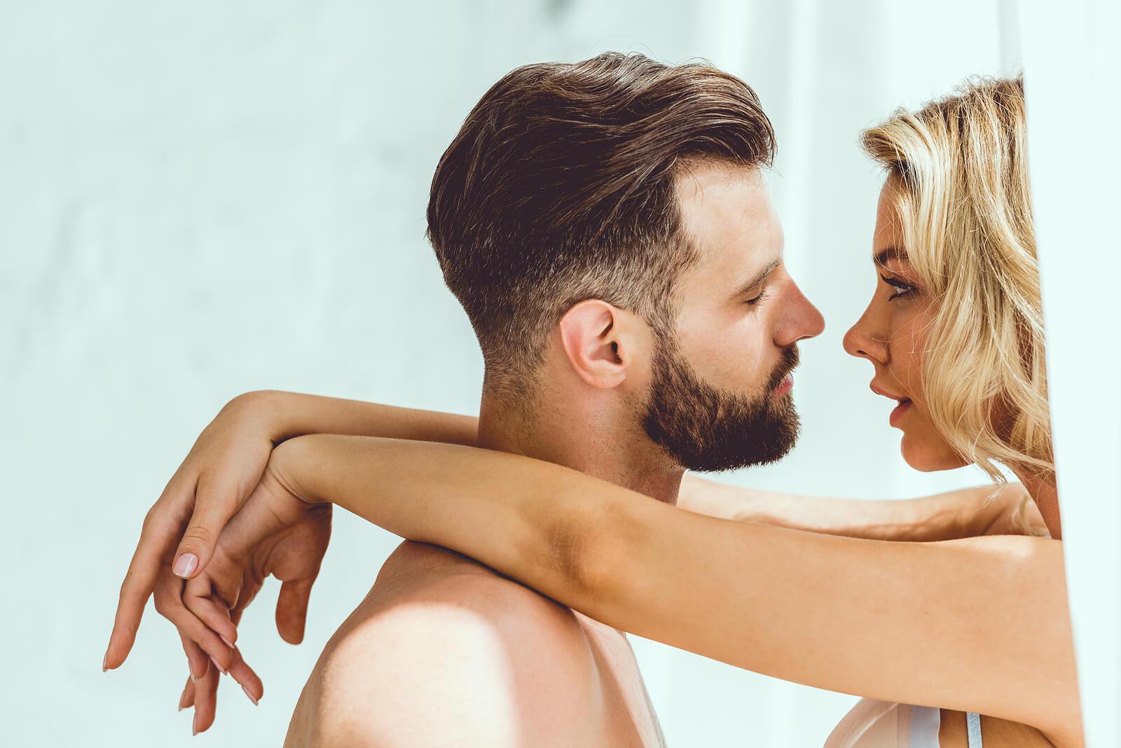 Pareja besándose mientras tiene sexo de pie.